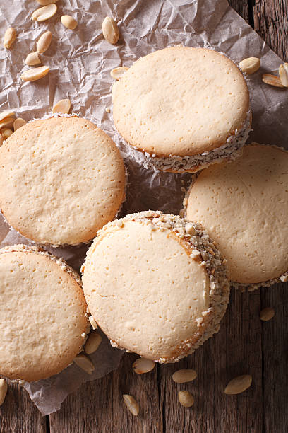 alfajores cookies on paper close-up on table. Vertical top view - foto de stock