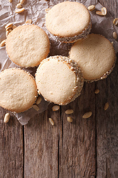 alfajores cookies on paper on the table. Vertical top view - foto de stock