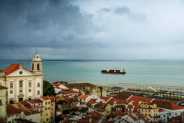 alfama district and tagus river in lisbon. - rain clouds porto portugal imagens e fotografias de stock