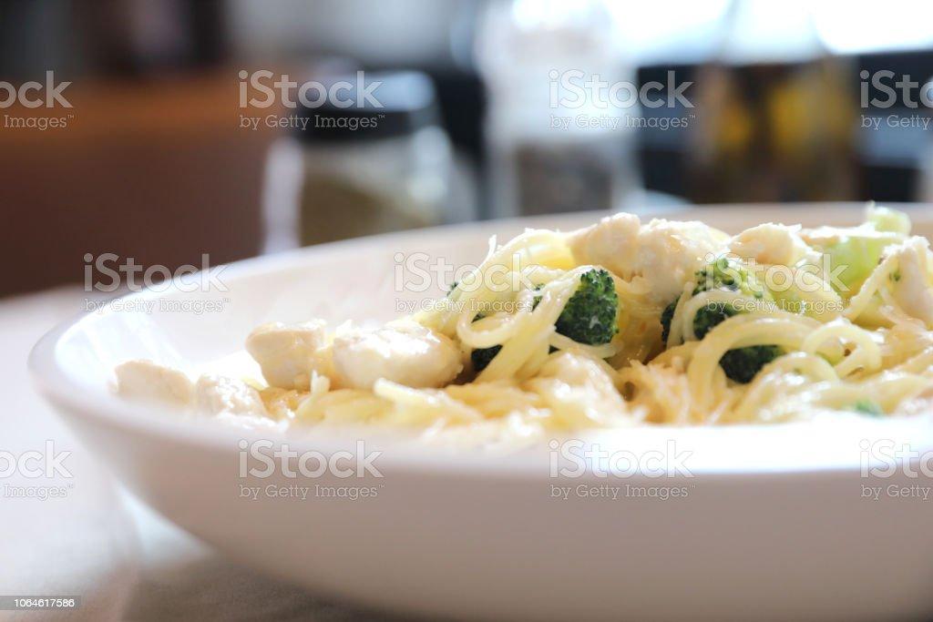 alfredo spaghetti broccoli chicken white sauce in restaurant background stock photo