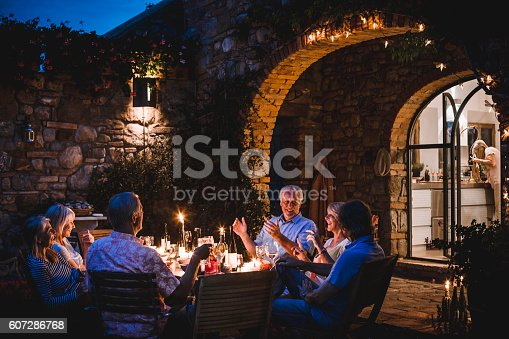 A group of mature friends are sitting around an outdoor dining table, eating and drinking. They are all talking happily and enjoying each others company as darkness falls. The image has been taken in Tuscany, Italy.