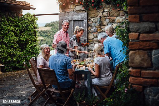 A group of mature friends are sitting around an outdoor dining table, eating and drinking. They are all talking happily and enjoying each others company. The image has been taken in Tuscany, Italy.