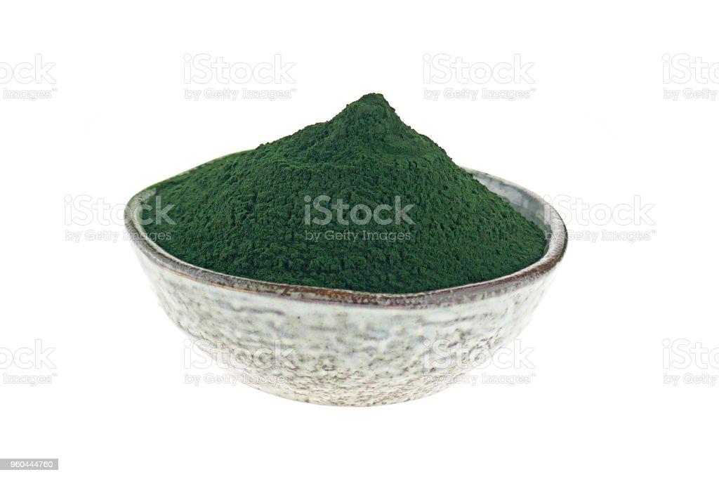 Las algas espirulina. Espirulina en polvo en un plato de cerámica aislado sobre fondo blanco. Concepto de comida Super. - foto de stock