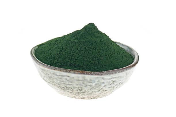 las algas espirulina. espirulina en polvo en un plato de cerámica aislado sobre fondo blanco. concepto de comida super. - algas fondo blanco fotografías e imágenes de stock