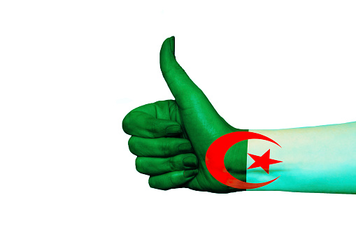 Algeria flag painted on hand showing thumbs up in isolated background