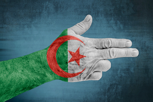 Algeria flag painted on male hand like a gun