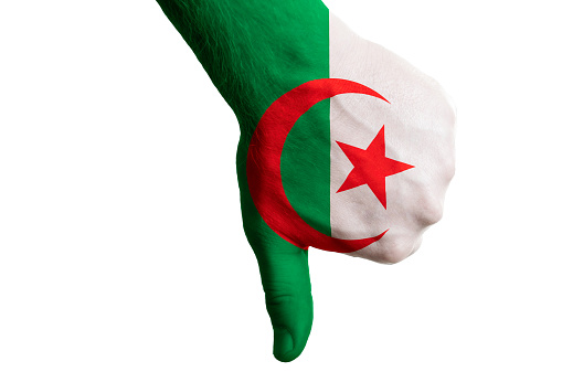Hand with thumb down gesture in colored algeria national flag as symbol of negative political, cultural, social management of country