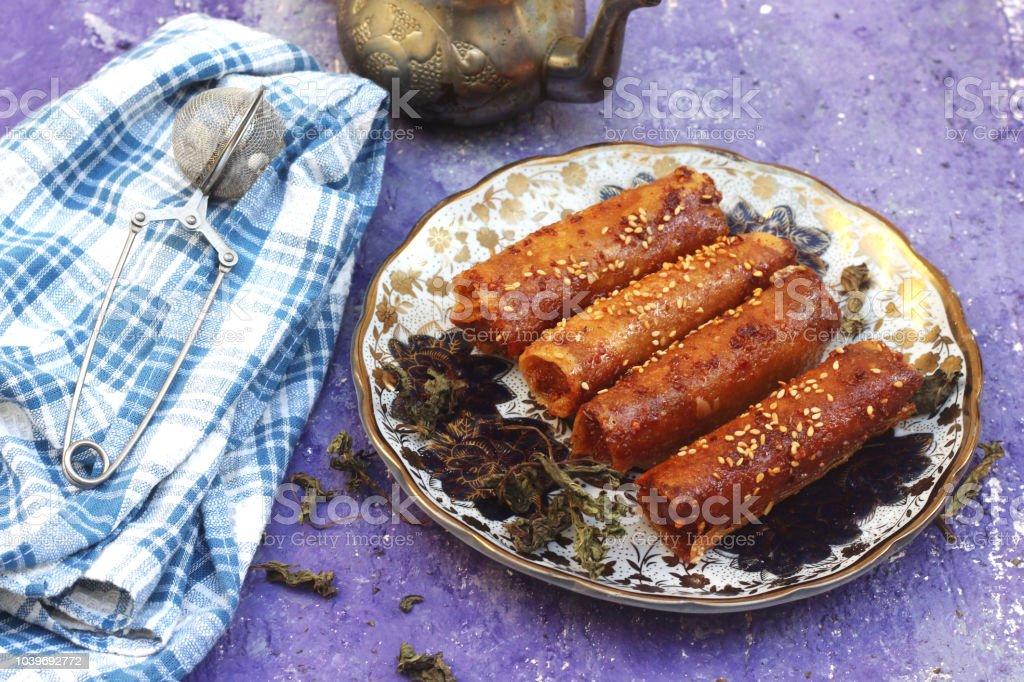 Pastas de almendra argelino cigarros dulce decoración con ajonjolí y té Árabe - foto de stock