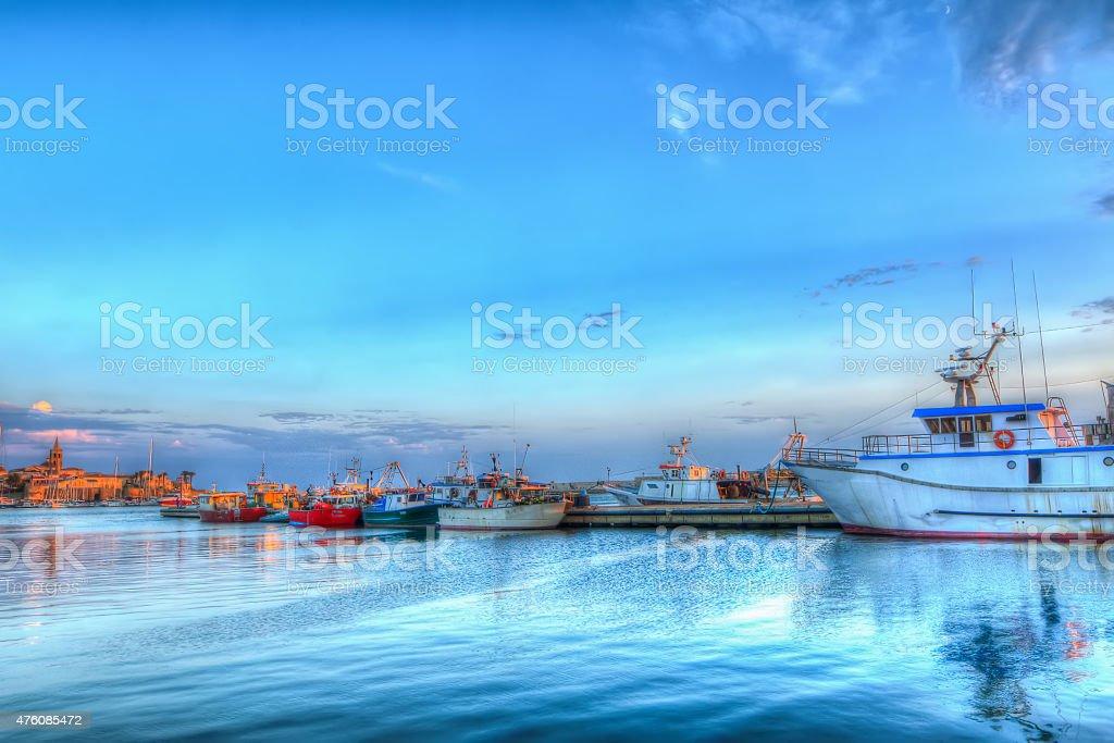 Alghero porto sotto un chiaro cielo al tramonto - foto stock