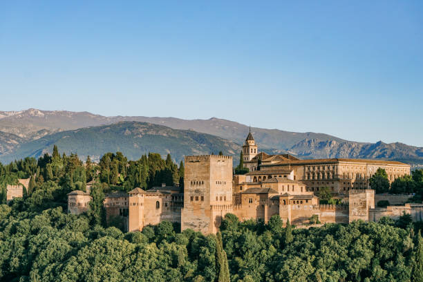 Alhambra Palace at afternoon General view of Alhambra Palace and Nevada Mountain at afternoon in Granada, Spain on May 20, 2017 palace of charles v stock pictures, royalty-free photos & images