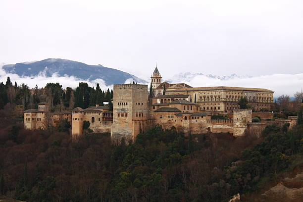alhambra Spain in winter clothes Granada alhambra Spain in winter clothes, snowcapped mountains of Sierra Nevada in the background, grey dramatic sky palace of charles v stock pictures, royalty-free photos & images