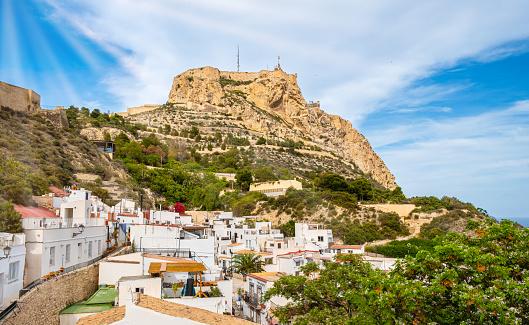 Alicante old town and Santa Barbara Castle on Benacantil hill. Narrow streets and white houses on hillside in ancient neighborhood El Barrio or Casco Antiguo Santa Cruz, Costa Blanca region in Spain