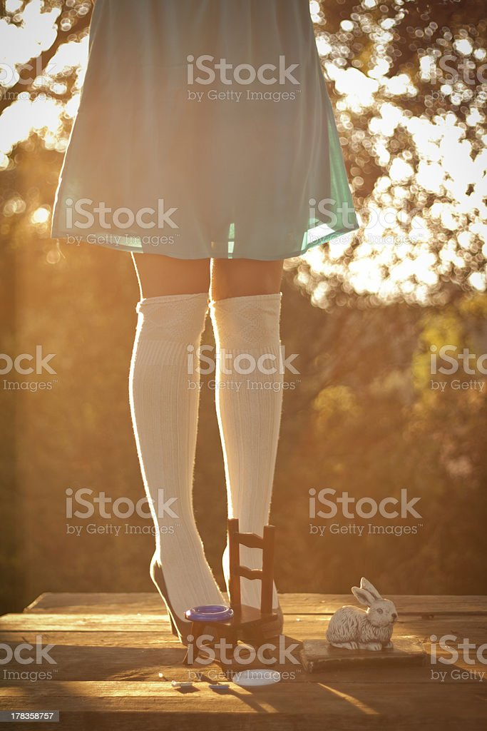 Alice in wonderland on a table with chair and bunny stock photo