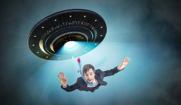 Alien abduction concept. Young man is abducted by UFO. stock photo