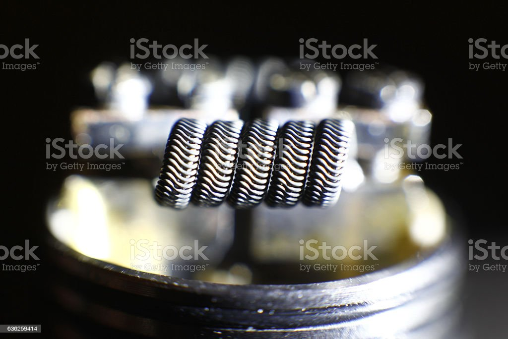 Alien coil build on vaping rebuildable dripping atomizer stock photo