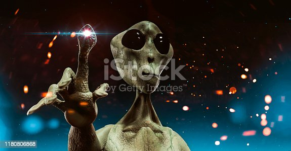 Alien with big head and large eyes stands still. He points with his finger and light emerges from it. The alien does not look friendly. Maybe is about to attack.