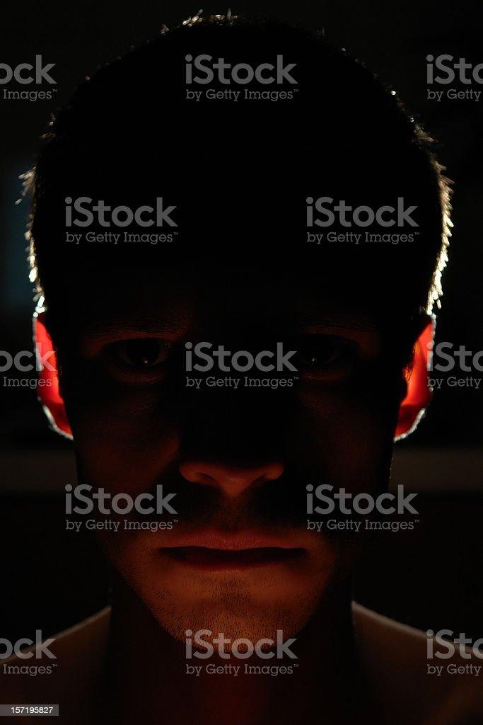 Alienation, portrait in darkness, man's head in back-lit royalty-free stock photo