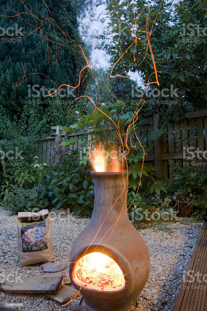 Alight chimnea and sparks in the back garden stock photo