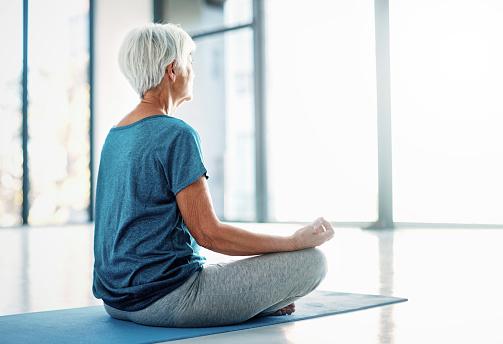 Rearview shot of a senior woman practising yoga indoors