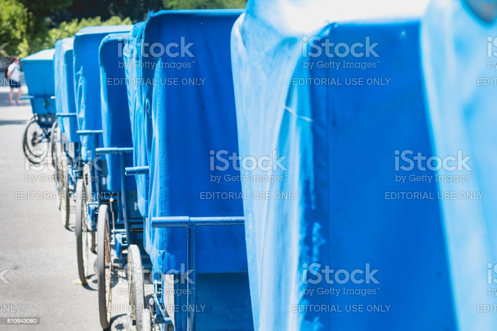 Alignment of blue wheelchairs in front of the swimming pools in the sanctuary in Lourdes stock photo