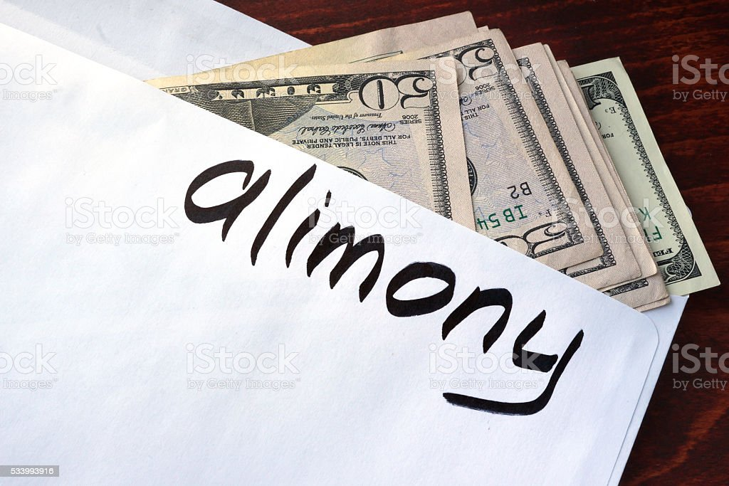 Alimony written on an envelope with dollars. stock photo