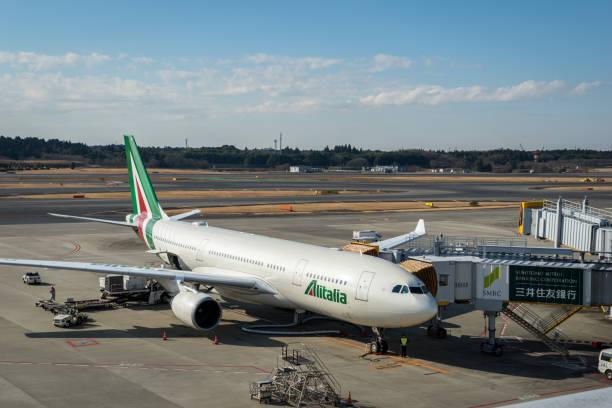 Alitalia aeronave Boeing 777 rebocado no Aeroporto Internacional de Narita, no Japão. - foto de acervo
