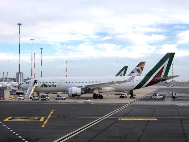 Aviões da Alitalia e Etihad (Airbus A330) estacionado o taxiway do Aeroporto de Roma Fiumicino (FCO). - foto de acervo