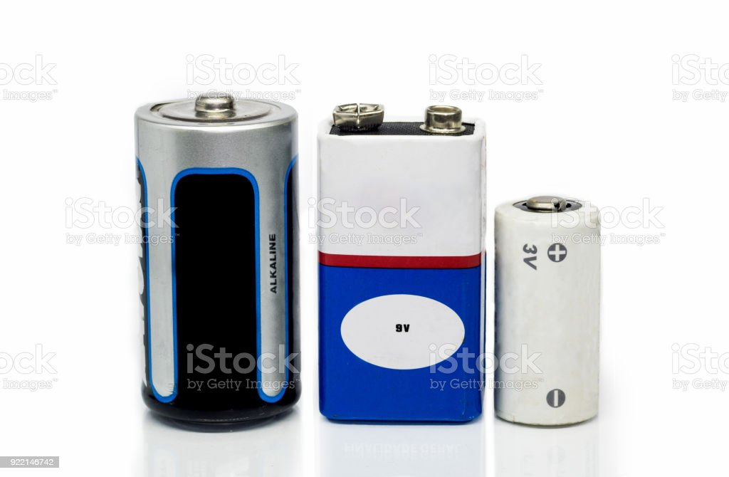 Alkaline batteries, 9v and 3v batteries, isolated on a white background with reflective surface stock photo