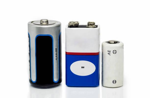 alkaline-batterien, 9v und 3v batterien, isoliert auf weißem hintergrund mit reflektierenden oberfläche - batterie stock-fotos und bilder