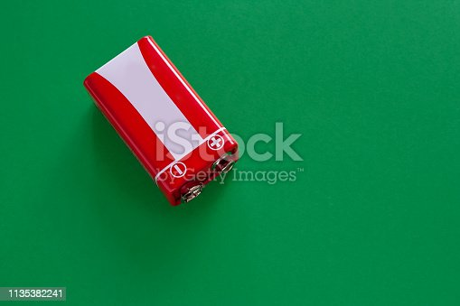 istock Alkaline Battery used crown on a green background. 1135382241