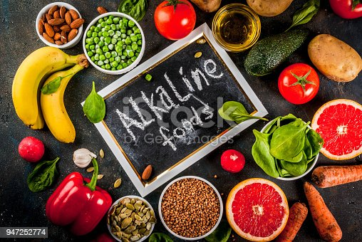 Healthy food background, trendy Alkaline diet products - fruits, vegetables, cereals, nuts. oils, dark blue concrete background above