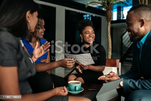 All african casual business meeting. Candid real happy moment between four work colleagues.