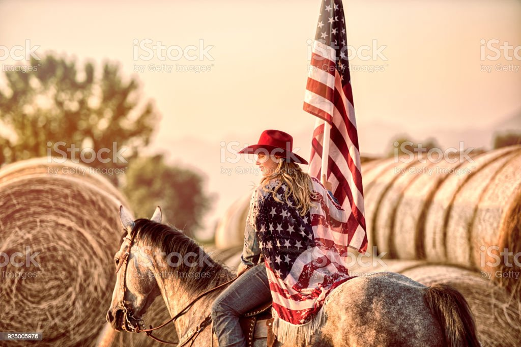 All American Cowgirl Wrapped UP In And Holding An American Flag. Country Patriotism.  She is riding her favorite horse and looking off in the distance.  Patriotic Scene. stock photo