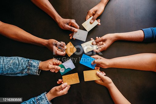 High angle shot of a group of unrecognizable people holding out their credit cards over a table