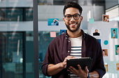 Cropped portrait of a handsome young businessman standing alone in his office and using a tablet