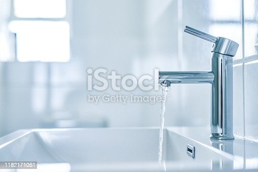 Shot of an open tap with running water in a bathroom at home