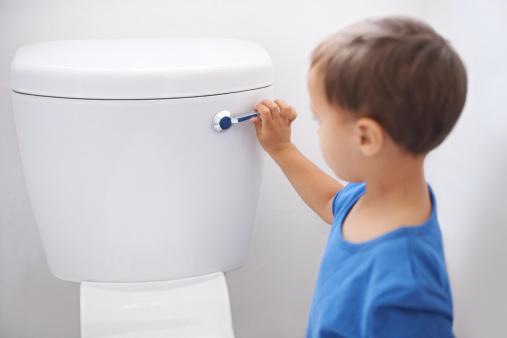 Shot of a cute young boy flushing a toilet