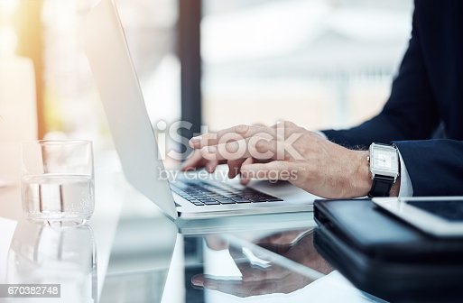 Shot of an unidentifiable businessman working on a laptop in an office