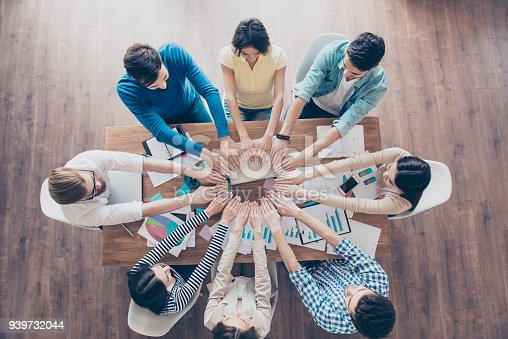 istock All for one! And one for all! Top up of colleagues putting their hands next to each other in a circle at their work place. All are wearing casual clothes.Team work and success concept 939732044