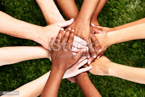 A pile of  multiracial hands are stacked in support or unity, against a background of grass. All for one and one for all!