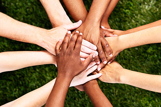 All for one! Hands stacked in unity and support A pile of  multiracial hands are stacked in support or unity, against a background of grass. All for one and one for all!  human rights stock pictures, royalty-free photos & images