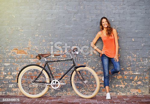 Shot of a young woman posing with her bicycle against a grey background