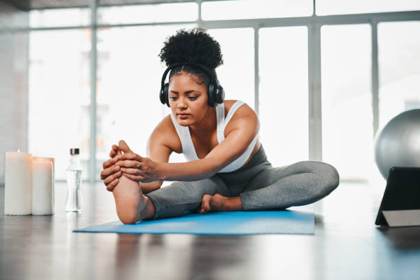 All I need is my mat and some therapeutic music Shot of a young woman listening to music while doing yoga touching toes stock pictures, royalty-free photos & images