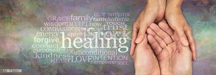 Female hands gently cupped around male open hands on a rustic muted multicoloured stone effect background with a HEALING word cloud