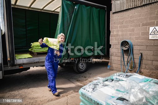 A front-view shot of a young caucasian female farmer, she is wearing blue overalls and picking up a large sack.