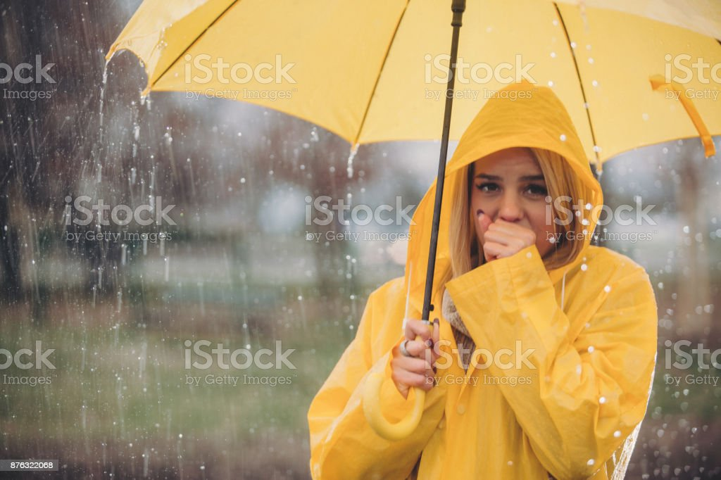 All in yellow woman standing on rain stock photo