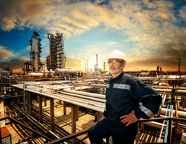 """All is under control """"Experienced engineer overlooking oil refinery plant in a sunset, dramatic sky colors"""" chemical plant stock pictures, royalty-free photos & images"""
