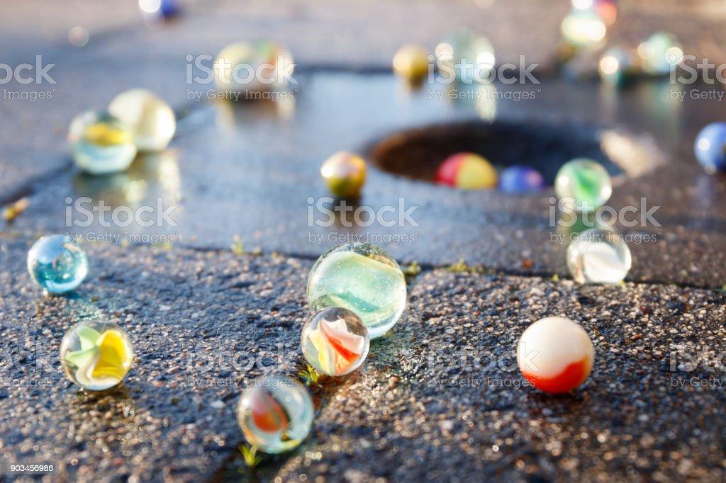 Alle Arten von farbigen Glasmurmeln im Licht der untergehenden Sonne auf dem Bürgersteig mit einem Marmor-Topf in der Fliese. – Foto