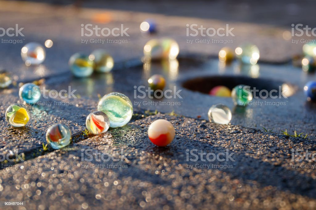 All kinds of colored glass marbles in the light of the setting sun on the pavement with a marble pot in the tile. stock photo