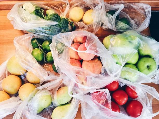toutes sortes de fruits et légumes dans des sacs en plastique - sac en plastique photos et images de collection
